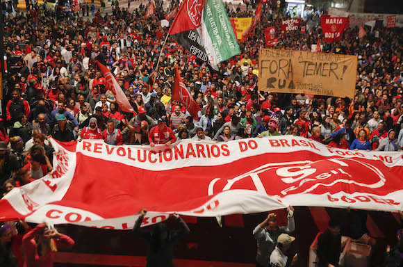 Thousands of demonstrators march during a protest organized by the workers roofless movement, against Brazil's acting President Michel Temer, and in support of Brazil's suspended President Dilma Rousseff, in Sao Paulo, Brazil, Thursday, May 12, 2016. In his first words to Brazilians as acting president, the former vice president promised to beef up the fight against corruption, and in particular said he will support the sweeping investigation into a mammoth kickback scheme at state oil company Petrobras. Temer himself has been implicated by witnesses in the probe, though he has not been charged. (AP Photo/Andre Penner)